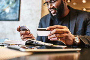 african american man holding debit card and mobile device