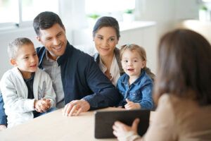 man and woman with boy and girl sit at bankers desk